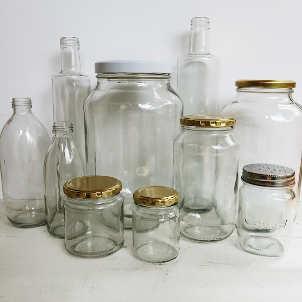 A variety of empty clear glass bottles and jars, various sizes.